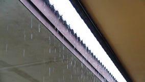 Dalende regen die van hoogste dak druipen aan op vloer stock footage