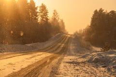 Dalende sneeuwvlokkenglans van zon boven weg stock afbeelding