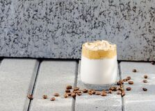 Dalgona coffee and coffee beans on grey concrete background.