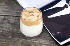 Dalgona coffee with open magazine on wooden background