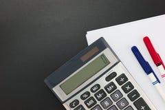 Dali bedrijfsfinanciënplaner Calculator, pennen en witte lege documenten op zwarte achtergrond stock afbeeldingen
