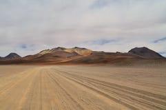 Dali's desert, surreal colorful barren landscape. Lonely unpaved road trough colorful Salvador Dali Desert in Altiplano, Bolivia Stock Images