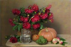 Dalie e frutti dei fiori in un canestro su un fondo marrone fotografia stock