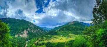 Dalin met huizen en een rivier in de bergen stock foto's