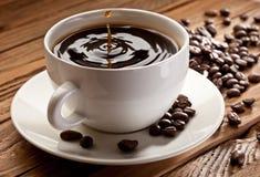 Daling die in een kop van koffie valt Stock Foto's