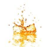 Daling die in oranje water met plons vallen die op wit wordt geïsoleerd stock foto's