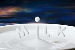 Daling of druppeltje die van de melk in een komhoogtepunt met brieven druipen voegde toe om ' Melk ' te maken Royalty-vrije Stock Foto's
