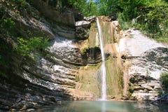 Daling onderaan kleine waterval in bergkloof Stock Foto