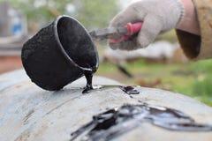Daling van teer van metaalkop op witte oppervlakte bij zware industrie stock afbeelding