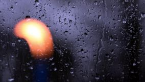 Dalingen die van Regen op Venster op een regenachtige dag, met een vage aangestoken kaars in de voorgrond vallen stock videobeelden