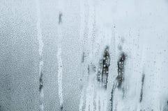 Dalingen en druppels van water op het glas De wintervenster gecondenseerd stock foto