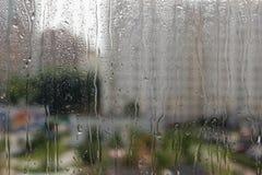 Dalingen van regen op glas tegen stadsachtergrond Stock Foto