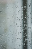 Dalingen van regen op het venster, regenachtige dag, onscherpe omheining in de rug Royalty-vrije Stock Fotografie