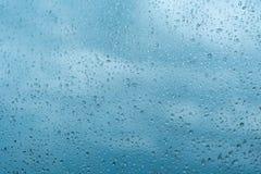 Dalingen van regen op het vensterglas Ondiepe DOF Venster na regen Blauwe Waterachtergrond met waterdalingen stock afbeeldingen