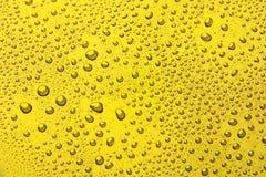 Dalingen van water op een kleurenachtergrond geel Royalty-vrije Stock Afbeeldingen