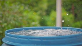 Dalingen van water van de dakdaling in een blauw vat stock video
