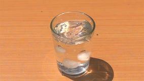 Dalings eigengemaakte die ijsblokjes in een glas met zoet water op een houten lijst wordt gevuld stock videobeelden