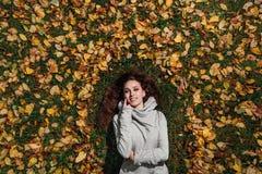 Dalingsportret van een meisje die op een gazon in een bospark liggen Lang haar op geel gebladerte Royalty-vrije Stock Afbeeldingen