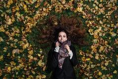 Dalingsportret van een meisje die op een gazon in een bospark liggen Lang haar op geel gebladerte Stock Fotografie