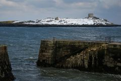 Dalkey island. Dublin. Ireland. Offshore island covered with snow with the ruins of an old church and a martello tower viewed from Colliemore harbour.. Dalkey Royalty Free Stock Photo