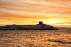 Dalky Island Snowy Golden Winter Sunrise. Dalky Island near Dun Laoghaire in County Dublin Ireland with its Martello Tower at dawn covered in winters snow Stock Image