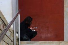 Dalla pioggia - donna irriconoscibile mora vestita nel nero si siede dentro area riparata il giorno piovoso che legge un opuscolo fotografia stock