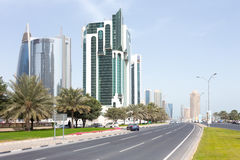 Dallah on Doha Corniche. DOHA, Qatar - February 11, 2015: The Corniche road with the Public Works Authority, Salaam Tower and Doha Bank tower Stock Photos