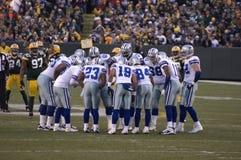 Dallas-Cowboys, die oben am Spiel-Tag Huddling sind