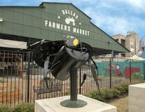 Dallas Farmers Market with whimsical bee, one of six metal sculptures, Dallas, Texas. Pictured is a whimsical bee, one of six metal sculptures in front of the stock image