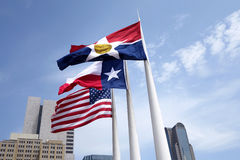 Dallas flags flying on flagpoles. Flags flying at noon over Dallas; United States, Texas, Dallas city flag Royalty Free Stock Photos