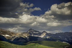 Dallas Peak, Tellluride, Colorado, Under Heavy Clouds. The sun-dappled crags of Telluride& x27;s Dallas Peak are burnished in amber and slate under heavy Stock Photography
