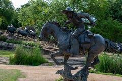 Dallas Teksas, Maj, - 7, 2018: Kowboja i longhornu krowy z bydłem w tle jako część punktu zwrotnego brązu bydła, Zdjęcie Stock
