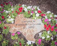 Welcome to Microsoft text on Texas map with flower decoration at office entrance. DALLAS, TX, US-APR 27, 2019: Texas state map and colorful flower bed decoration stock photo