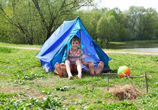 Dalle tende sul prato i piedini attaccano fuori e ragazzo Immagini Stock Libere da Diritti