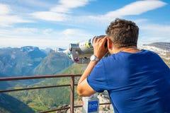 Dalsnibba, Noruega - 26 06 2018: Homem que olha nos binóculos no ponto de vista Dalsnibba, vista do fiorde de Gejranger, Noruega imagens de stock