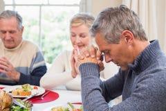 Dalsza rodzina mówi grację przed boże narodzenie gościem restauracji Fotografia Stock