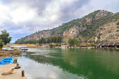 Dalyan canal and boats in the canal with rock graves of ancient royalty free stock images