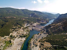 Dam across river in mountains. Aerial view of dam across river in mountainous landscape royalty free stock images