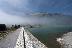 Dam of Aubert Lake and Neouvielle peak surrounded by cloud Royalty Free Stock Photos