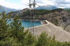 Dam and electricity pole, Lake Serre-Poncon, French Hautes-Alpes. Lac de Serre-Poncon is a lake in southeast France and one of the largest artificial lakes in stock images