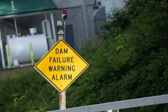 Dam failure warning alarm sign alerts drivers to any breakage or. Spills from the nearby water dam in Alaska stock image