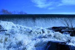 Dam with flowing water. Blue sky on background Stock Image