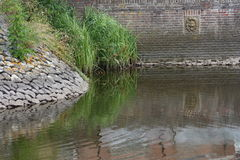 Dam. Fortified dam with large stones and reed beds stock images