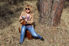 Dam-fotograf med gammalt kamerasammanträde på en tappningresväska i torrt gräs Arkivbilder