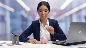 Dam i businesswearen som sätter myntet i piggybank, besparingar för framtid, bankinsättning arkivfilmer