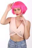 Dam i den rosa peruken som trycker på hennes huvud close upp Vit bakgrund royaltyfri bild