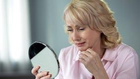 Dam i hennes 50 som ser i spegel som minns ung och sund hud, nostalgi fotografering för bildbyråer