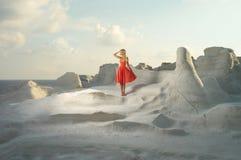 Dam i röd klänning i ett ovanligt landskap royaltyfri bild