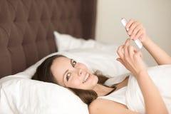 Dam i sängmessaging med smartphonen efter wakeup Royaltyfri Bild