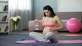 Dam i slutskeden av havandeskap som gör yoga, dricksvatten, säker barnsbörd arkivfoton